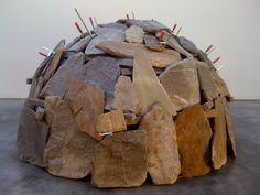 """""""Igloo Ticino"""" Mario Merz (1990) Pierres, métal Mario merz est issu du courant arte povera qui consiste à transformer des matériaux insignifiants en productions artistiques. L'igloo est une représentation primitive de la maison. Mario Merz emploi simultanément la roche (utilisée depuis l'âge de pierre) et des serre-joints modernes, confrontant le passé et le présent. Cette construction précaire rappelle que la problématique autour de l'abris est toujours d'actualité."""