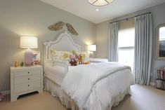 source: MALI Chic big girl's room with gray walls framing white princess headboard with nailhead trim and bed rails. Carved wood angel wings over white headboard paired with soft white bedding, white pleated bed skirt and white and yellow pillows flanked by white 3-drawer nightstands accented with lilac lamps/ Sweet girl's bedroom with pinch-pleat light-blue curtains layered over matchstick roller shades and and antique arched mirror over bookcase.