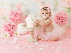 adorable girl's first birthday cake smash photo, cupcake, frosting, flowers, flower, party, celebration, turning one year old, flower pedals, pink floor, outfit, flower backdrop, background, headband little girl, daughter, GilmoreStudios.com