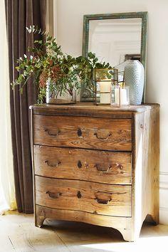 Cómoda antigua de madera con espejo, poravelas y jarrón con flores_412730