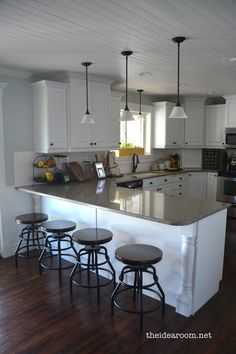 dark floors, white cupboards, neutral counter, wood ceiling... very pretty, and not over the top.