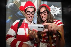 Costumed fans marvel at a new movie trailer on  one of LG Electronic's mobile phones.