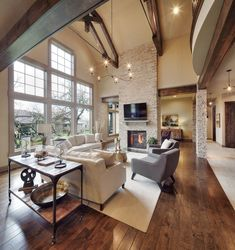 Rustic great room, reclaimed wood beams, wire chandelier, natural stone fireplace, rustic wood floors, two story living room | Dwell Interiors