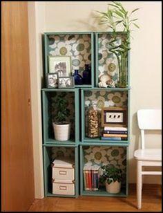 nichos/caixas de madeira pintadas com o fundo forrado. Fica uma estante linda e original