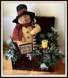 Large Asian wooden box w/prim snowman holding peppermint stcks and a prim sign.  Embellished with frosted ming pine, lacquered berries,rusty jingle bells & a wax coated flicker candle.  $65