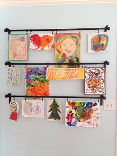 Children's art displayed with IKEA curtain rods