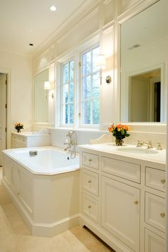 Dreamy bathroom with matching white vanities flanking a drop in spa tub with paneled surround.