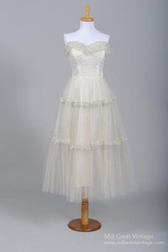 Designed in the 50's, this sweet vintage wedding dress is done in a silver trimmed and ruffled tulle over an additional layer of tulle and is lined in silk t...