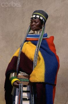 South Africa - Ndebele woman in traditional dress. Women of Ndebele people wear brass rings called 'idzila' around their neck, legs, and arms.