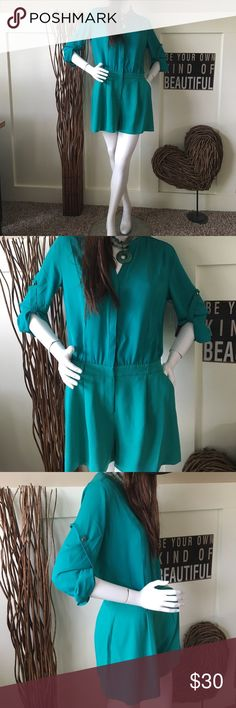 Jennifer Lopez emerald green jumpsuit Jennifer Lopez emerald green jumpsuit is one piece but looks like two   It has  roll up sleeves that give you versatility on cooler days. The full shorts are flattering to show off your pretty legs and almost look like a skirt. Jennifer Lopez Pants Jumpsuits & Rompers