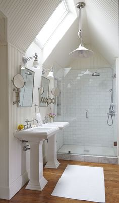 An Attic Space Is Reclaimed With This Bathroom Remodel. Simple White Subway  Tiles Are Offset With Marble Shower Base. The Pedestal Sinks Give The  Bathroom A ...