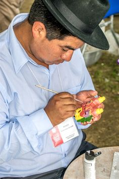 A shot of a Peruvian artisan hand painting intricate detailing onto a clay piece at the 2015 Smithsonian Folklife Festival on the National Mall in Washington, DC. || #AlexTonettiPhotography #Photography