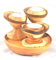 Trio of tea-light holders from a branch of yew on a yew base.