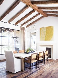 Spanish Revival Elements - beams, metal windows, plaster walls | large yellow artwork above fireplace | large windows | residential interior design ideas