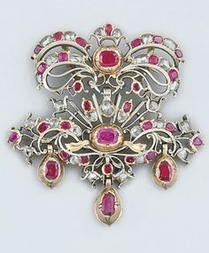 A late 18th century Iberian, ruby and diamond brooch. Composed of a closed-set ruby and rose-cut diamond openwork cluster bow panel, suspending a matching floral spray panel with three ruby single stone drops in silver-gilt mount, circa 1790, probably Spanish.