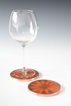 MANDALA Coasters: Copper - The floral design of these coasters is inspired by the flower patterns created using a pencil compass. Each petal has been carefully hand pierced out of copper sheet before being spun around the felt that peeps out through the little windows and acts as a soft base to protect your table. Photograph: In Two Dimensions Photography.