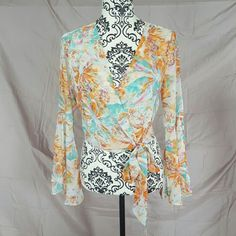 JUST IN Floral Bell Sleeve Boho Top Gorgeous multi color floral top! New with tags! Tie waist and split bell sleeves. 100% Polyester. There is an inside tie and the one you see on the outside-both adjustable for a perfect fit! It is a gorgeous, light chiffon material. It is a light, Cream color with orange and teal floral print. Available in S, M, L. Oh My Julian Tops Blouses
