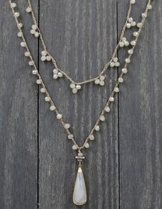 Opalescent creamy colored crystal glass beads are hand knotted in a single pattern to create this very versatile piece. Looks great layered with other Coastal Fog products or by itself for a simple statement. Necklace measures 22 inches. Shown with other Coastal Fog products for layering ideas.