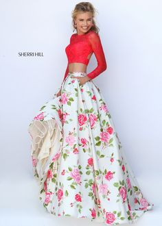 This graceful two piece ball gown features a lovely floral print ball gown skirt with hidden side pockets. The elegant lace top features long sleeves and a cut out open back. Sherri Hill style 50261 is part of the current Sherri Hill evening dress collection. This is a beautiful choice for your winter formal, prom, or any special occasion.