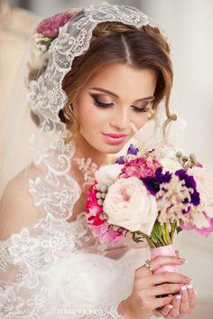 Романтический образ невесты выражен в прическе из длинных локонов собранных в пучок на затылке с плетением и цветами, с фатой - фото 2267330 Свадебные стилисты Art4Studio