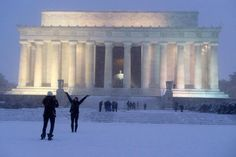 Visitors pause to take pictures in front of the U.S. capital's Lincoln Memorial Friday as the storm set in.