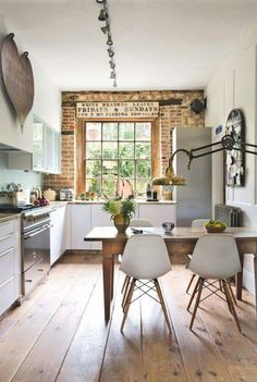Modern rustic kitchen with wood floors, brick wall, white chairs and brass lamp