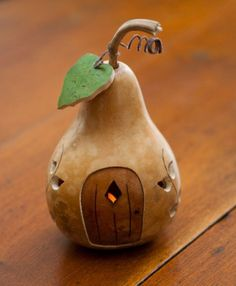"""Our newest design in our Cottage Series is a little garden shed.  It features an ivy cut-out design, and is natural in color with a walnut door.  A gourd leaf completes the Garden Shed. Approximately 4"""" in diameter.  Add the optional tea light to create a warm glow.Please note:  If a tea light is purchased, the gourd will sit  over the tea light and will not fit snugly in the gourd.  The Garden Shed gourds will ship the first week of April."""