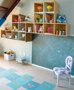 Os avós projetaram este cantinho especialmente para organizar a bagunça dos netos. A lousa na parede e amarelinha pintada no chão deixam tudo mais divertido. A estante ajuda a organizar os brinquedos