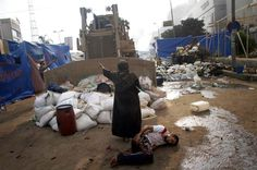 A woman tries to stop a military bulldozer after clashes between security forces and opposition groups left hundreds of people dead in Cairo 2013.