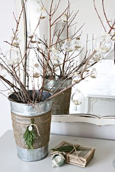 burlap wrapped around silver bucket. branches are holding clear glass ornaments full of buttons!