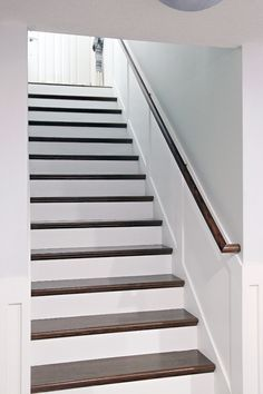 Do it Yourself: Stairway Handrail Installation, stairs with carpet ripped out - risers painted white and steps stained, board and pattern moulding / molding on walls, nice wood railing