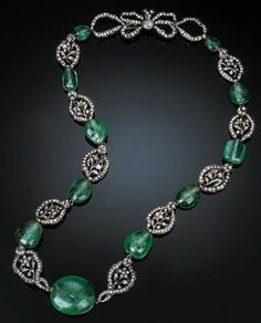 AN EARLY 19TH CENTUR EMERALD AND DIAMOND-SET NECKLACE  Comprising ten closed-back rose-cut diamond-set openwork floral clusters separated by eleven polished emerald beads to a rose-cut diamond-set bow clasp, mounted in silver and yellow gold, French import mark, numbered 3582, 58 cm long