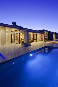 Rear view of luxury villa at night time with swimming pool.