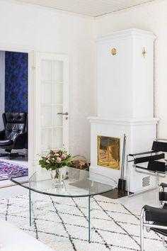 Lasipöytä oli aikaisemmin Leena-siskon toimistossa. Eeva olisi halunnut kaakeliuunin, mutta lopulta päädyttiin Cronspisenin Duo 103 -takkaan, joka on maalattu Tikkurilan korkeakiiltoisella Helmi-maalilla, sävy Pro Gry 1964.