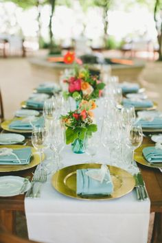 white runner, gold chargers and pale blue napkins. Design by Little Blue Box Weddings.