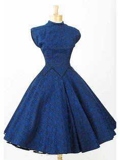 "Ultra-glamorous, authentic 1950s, one of a kind ""New Look"" party dress in a gorgeous blue lacey floral pattern heavyweight brocade against a black satin background."