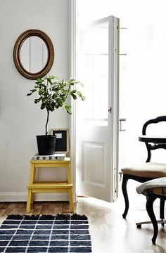 A pop of colour with a mustard/sunflower yellow stool. An Ikea employees apartment in Sweden - desiretoinspire.net