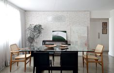 A sala de jantar tem apenas cores neutras: cinza no piso de cimento queimado, preto no aparador e nas cadeiras e muito branco nas paredes e cortinas. Projeto da arquiteta Julliana Camargo