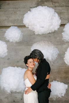 LGBTQ couple standing together in front of DIY cloud wedding backdrop