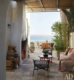 The stone terrace is furnished with rattan and wicker chairs and an early-20th-century octagonal table painted deep red; the large ceramic j...