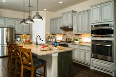"Open kitchen with colored cabinets that are both timeless and ""now"" :: M/I Homes of Austin: Caballo Ranch - Brenham Model"