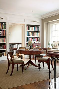 In the library of a Long Island home designed by Mariette Himes Gomez, English chairs—one holding the family Chihuahua—surround a Georgian-style table. ARCHITECT: Kean Williams Giambertone DESIGNER: Gomez Associates Inc. Architectural Digest, Long Island, Colonial Mansion, Library Table, Library Room, Dream Library, Traditional Office, Home Libraries, Home Decor Inspiration