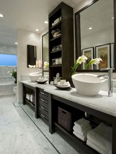 "Even the most well-appointed, high-end bath must offer practical features. To help this one serve the dual masters of style and substance, designer Wendy Ann Miller created dual vanities with a mix of closed and open storage, topped with sculptural vessel-style lavatories. The result, says the designer, is ""a sophisticated space with timeless appeal, that suits the homeowners' needs for both function and luxury."""