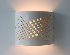This wall light is hand made of white stoneware. The light reflection of the lamp shines upwards and downwards. The cutting design of the holes
