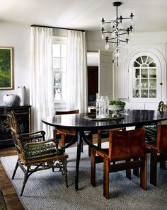 The built-in wooden cabinet and wood panel floors were original to the house and were polished back to life. The dining table is by Rose Tarlow, and the two Victorian wicker chairs, which were re-covered in green leather, are from a Chicago vintage company called Revival.