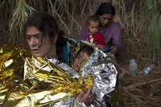 A Syrian refugee and a baby are wrapped with thermal blankets moments after arriving on an overcrowded dinghy on the Greek island of Lesbos after crossing a part of the Aegean Sea from the Turkish coast, September 28, 2015. A record number of at least 430,000 refugees and migrants have taken rickety boats across the Mediterranean to Europe this year, 309,000 via Greece, according to International Organization for Migration figures. REUTERS/Dimitris Michalakis