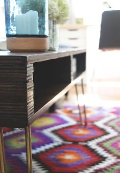 Hellooooooo! I'm back today with the most-requested project from my living room makeover—the DIY storage coffee table! We've been living with this table for a few weeks now and I have to say…we love it. It provides the perfect amount of storage for our needs without looking bulky, and the stained birch plywood and brass …