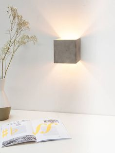 """Very nice wall light which makes a indirect light up and down the wall. The Inside is gold. Available inside colours: gold, silver, copper or neutral.The cubic pendant lamp [B3] is cast from a light gray concrete. It combines noble gold with rough concrete into a timeless and elegant designer lamp. The high quality gilding of the insides emits a pleasant warm light. With an edge length of 14 x 14 x 14 cm, the lamp is suitable both,individually as to """"looker"""" but also in series in a long…"""