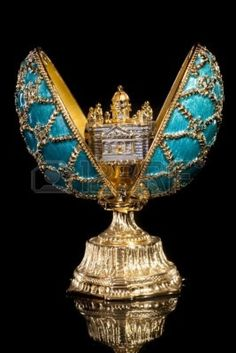 gold and cerulean blue Fabergé egg containing a small castle
