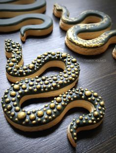 Snake cookies by Tammy Holmes.  Decorated cookies, snakes, glam snakes, designer desserts, gold and black, icing cookies, unique desserts